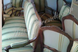 Un canapé et des chaise et fauteuils couvert avec tissu vert jaune beige en rayures avec differents dossiers