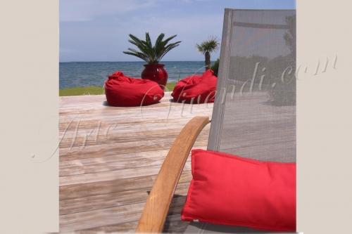 salon extérieur la mer coussins rouge sur transat gris