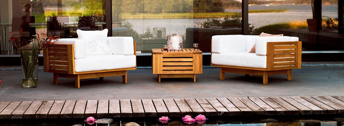 Terrasse devant l'eau avec chaises et coussins couleur blanc et bois
