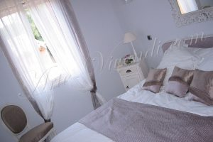 Chambre d'amie romantique rideaux chaise tete de lit coussins couvre lit couleur mauve et blanc